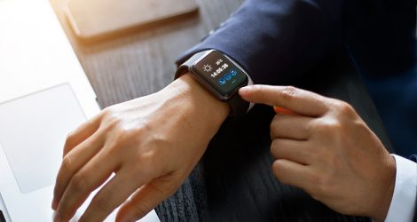 Wearables in business - Businessman using smart watch app over laptop and smartphone on working desk